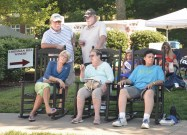 Several festival goers relax in rocking chairs during the picnic.