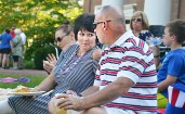 In the shade of Old Center, Susan Bloom, left and Amy and Rusty Chaney enjoy the picnic.