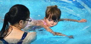 Photo by ROBIN HART/robin.hart@amnews.com Kally McCowan blows bubbles in the water as swim instructor Katie Lamb holds her in place.
