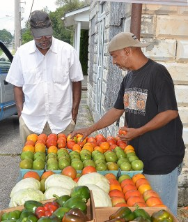 Anthony Ford, left, looks over fresh tomatoes that Terry Doneghy was selling Tuesday afternoon. Ford had just gotten off from Burke's Bakery where he's worked for 41 years. Doneghy said he and Ford were in high school together, but hadn't had a chance to visit for a long time.