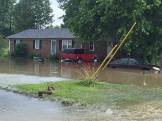 Photo courtesy of Boyle County Emergency Management Water floods a house and a pair of vehicles in the area of Old Hustonville Road and Castlerock Sunday.