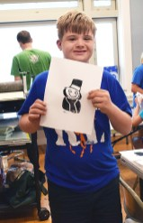 Tye Smithers of Danville proudly displays the print he created in Cross-Training for Artists camp.