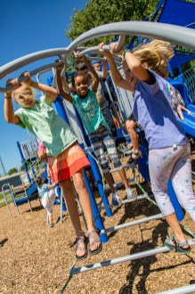Ben Kleppinger/ben.kleppinger@amnews.com From left, June Goodwin, Aleah Porter and Ally Schommer bounce on a rope-and-metal ladder on the new playground.