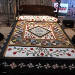 A quilt is displayed on a bed.