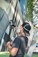 """Ryan """"ARCY"""" Christenson, of Connecticut, paints a detail on his mural Saturday."""