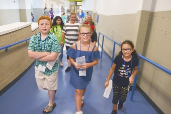 From left, Gage Ross, Katie Kelly and Ella Tompkins, all former students at Jennie Rogers Elementary School, lead the first tour through the Edna L. Toliver Intermediate School following a grand opening ceremony Friday afternoon.