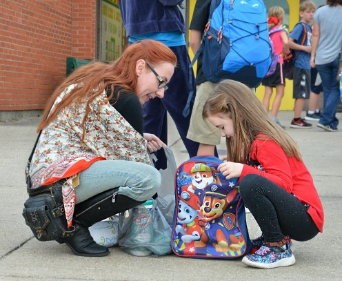 Janie Bradshaw, left, helps her daughter, Lela, put last minutes items into her backpack Wednesday morning.