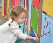 Photo by Robin Hart/robin.hart@amnews.com Kinsley Llamas, 3, carefully paints short strokes of color on a small section of the mural Saturday.