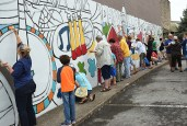Photo by Kate Snyder More than 100 people turned out to begin painting a mural on the side of Raggs' building on Third Street Saturday morning