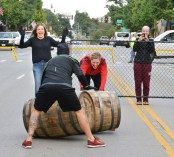 Jennifer Kirchner, executive director of the Danville-Boyle County Convention and Visitors Bureau cheers with delight at two Bourbon Chase runners collide as they compete in a friendly barrel rolling competition. (File Photo)