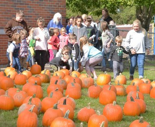 Robin Hart/robin.hart@amnews.com Fifth grade students at Perryville Elementary School assist kindergarteners in choosing their pumpkins Monday afternoon. Some of the pumpkins weighed as much as the younger kids.