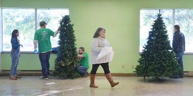 Robin Hart/robin.hart@amnews.com At center, Beth Marlowe, manager of Blue Bird Market which helps support the Wilderness Trace Child Development Center, walks past Christmas trees that Heart of Kentucky United Way volunteers were assembling on Wednesday.