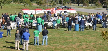 Following the Heart of Kentucky United Way Day of Caring, volunteers from Boyle, Lincoln, Garrard and Mercer counties gathered at Millennium Park for a luncheon. Before eating the group stands during the Pledge of Allegience.