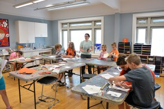 Lindsey Sweis, an instructor at the Community Arts Center's fall break camp, encourages her students to start cleaning up after working on an arts project on Wednesday.