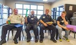 """Ben Kleppinger/ben.kleppinger@amnews.com From left, Boyle County Fire Chief Donnie Sexton, correctional officers Mike Long and John Hall and Campbellsville University student Brandon Bergman sit in """"jail,"""" watching other participants and waiting to be released."""
