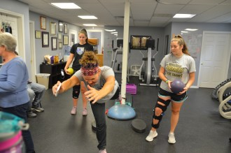 Photos by Bobbie Curd/bobbie.curd@amnews.com Physical therapist Gina Motley, front, shows Danville soccer player Ella McKinney, left, and Kolie Gardner, a Boyle County soccer player, exercises in order to rehabiliate their ACL.
