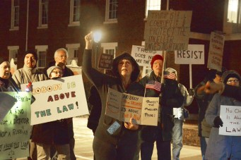 """Dana Bullock holds a sign stating """"Nobody is above the law"""" and """"Protect the Mueller probe"""" during Thursday night's nationwide protest."""