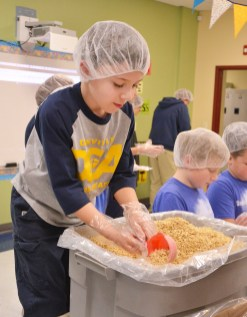 Robin Hart/robin.hart@amnews.com Noah Carroll gets a scoop of dried soy protein to add to the meals that DCA students were packing on Giving Tuesday.