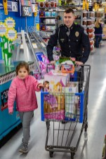 Ben Kleppinger/ben.kleppinger@amnews.com Danville Police Officer Nathan Brown pushes the shopping cart as 5-year-old Ady, a Hogsett Primary School student, looks for more toys.