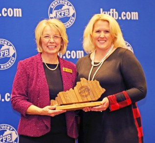 Photos contributed Megan DeHart of the Mercer County Farm Bureau Women's Committee, accepts the 2018 Gold Star Award of Excellence from Vicki Bryant, chair of the Kentucky Farm Bureau state Women's Committee. The award was presented during a November 30 recognition program at the 99th Kentucky Farm Bureau annual meeting.
