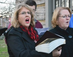 "Aprile Hunt sings with a group following the ""historic"" swearing in ceremony in front of Kentucky's first courthouse at Constitution Square Monday evening. Hunt is also the wife of newly sworn-in Boyle County Judge Executive Howard Hunt."