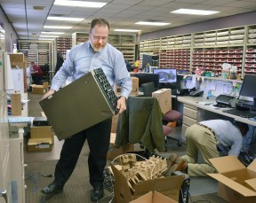 Dave Gripp, operations technician with Software management, lifts a server to place under a desk in the County Clerk's office on Thursday. Photo by Robin Hart.