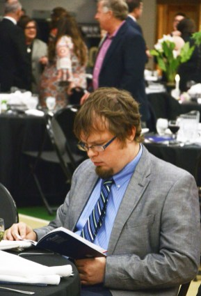 Warren Lilly studies the awards program. Photo by Robin Hart.