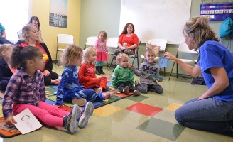 Teacher Mary Wells talks to the group of 3-year-olds about the letters writtin on the card.Photo by Robin Hart.