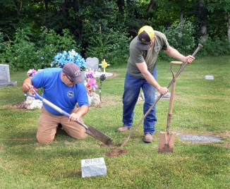 At left, Darin Horton and Cemetery Supervisor Json Turner dig a hole to place a granite marker in Thursday morning. (Photo by Robin Hart)