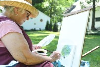 Sarah Witsee creates a painting during the garden tour in Danville on Saturday. (Photos by John Scarpa.)