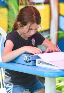 Isabella Phillips, age 9, loads paper into a typewriter at the pop up park in downtown Danville on Saturday (Photo by John Scarpa)