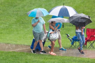 Festivalgoers who tried to wait out the rain make their way off the lawn at Center College, shielding themselves from the downpour with umbrellas. (Photo by Ben Kleppinger)