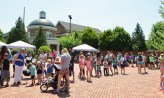 Students and adults line up to receive free hotdogs and popsicles and face painting during the library's summer reading program kickoff event on Monday. (Photo by Robin Hart)