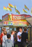 A group of boys line up for a ride at the fair with a colorful carnival food booth in the background. (Photo by Robin Hart)