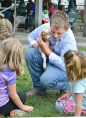 Grant Holman, 10, of Perryville, holds his friend's orphaned kid as other children gather around. Holman was showing his goats at the Boyle County Fair Wednesday night. (Photo by Robin Hart)