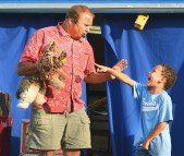Elijah Cline, 7, of Danville laughs at a magic trick that Mark Comley just performed with his puppet dog during a show at the Boyle County Fair Tuesday night. Comley will be performing two magic shows every night during the fair and is included with the price of admission. (Photo by Robin Hart)