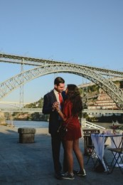 lovers dacing at ribeira do douro with D Luis bridge behind