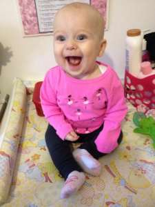 smiley sitting baby in pink shirt