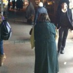 Jewish woman in Jerusalem shuk wearing cloak.