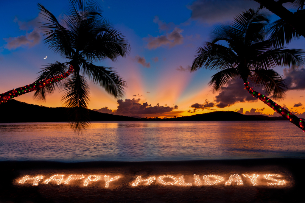 Happy Holidays made with Christmas lights at a tropical beach