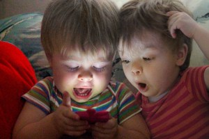 Two babies using a smart phone