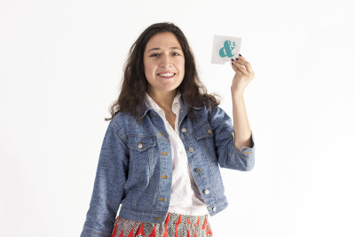 Christina Campodonico holds up Ampersand's official logo — a seemingly hand-painted turquoise Ampersand