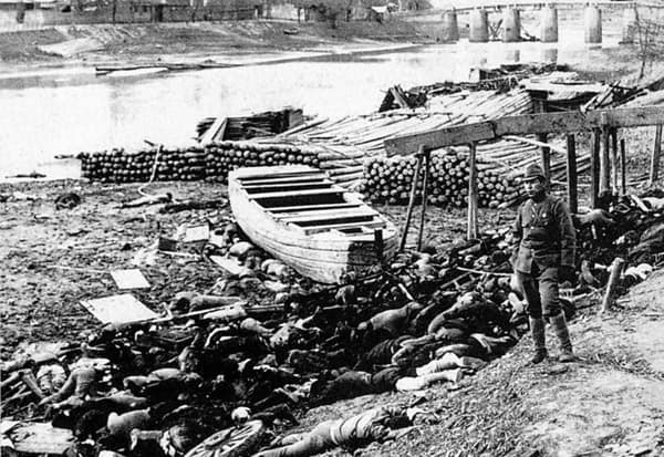 A Japanese soldier stands next to Chinese victims of the Nanking Massacre.