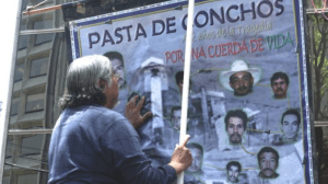 Family members hang a poster to remember Pasta de conchos mine workers killed in gas explosion