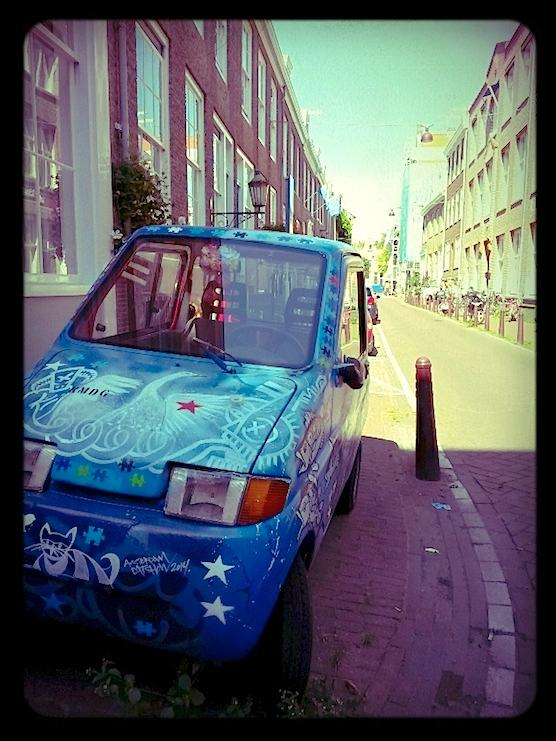 Street Art in Amsterdam. A small car is filled colorfully painted.