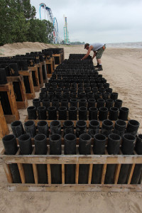 Chris Linder of Zambelli Fireworks places mortar tubes along the beach in preparation for Cedar Point's Fourth of July fireworks.