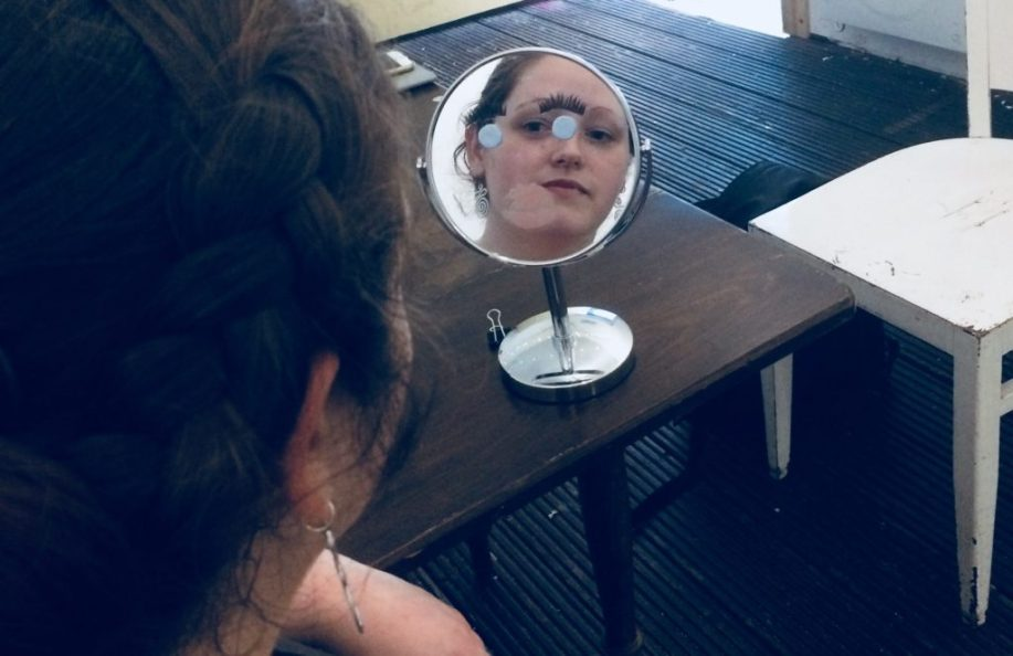 Amy looks into a hand mirror, reflecting her own face. The mirror also has a drawn-on face representing Helen of Troy.