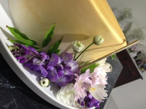 Canted angle shot of side of 1-tier gold fondant cake with purple wisteria, pale pink and white daisies, and daisy buds on a white round platter