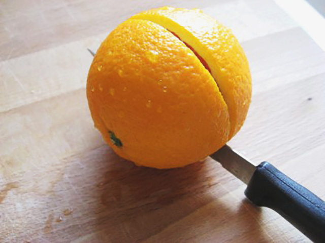 Knife slicing an orange