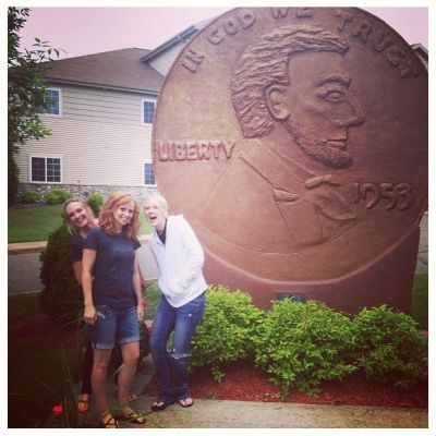 Women next to a giant penny
